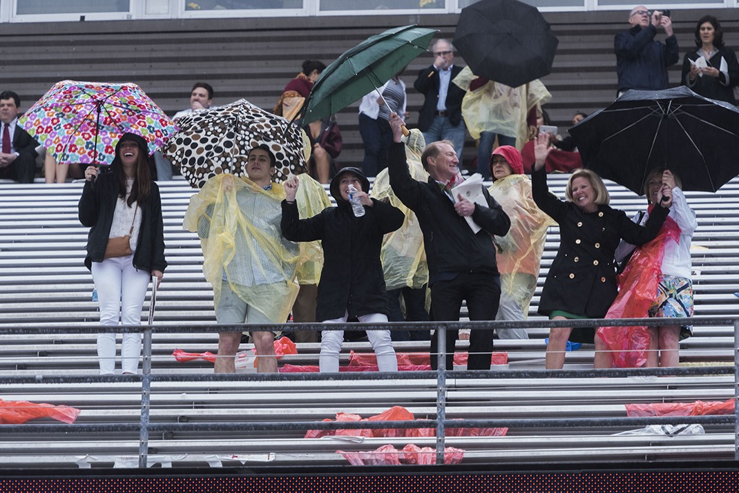 Family members dancing with umbrellas in the stands