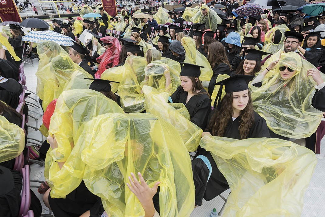 Scene from Alumni Stadium at BC Commencement; umbrellas and students in rain ponchos