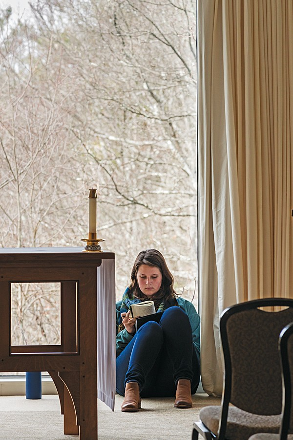 Ellen Hill writes in her journal in the Connors Center's chapel