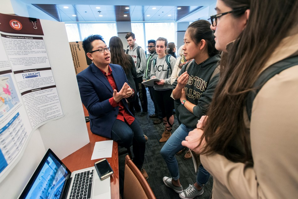 Undergraduate Poster Session for the Humanities in the Reading Room of O'Neill Library. Richard Balagtas A&S '16 explains his project to Allicen Dichiara A&S '16, graduate student Rachael Tully, Lauren Lin A&S '18, and Kejs Aliko A&S '18.