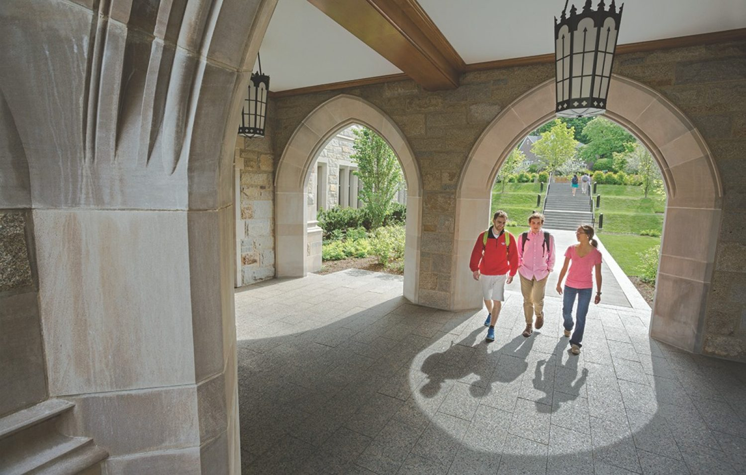 Students walk through arches