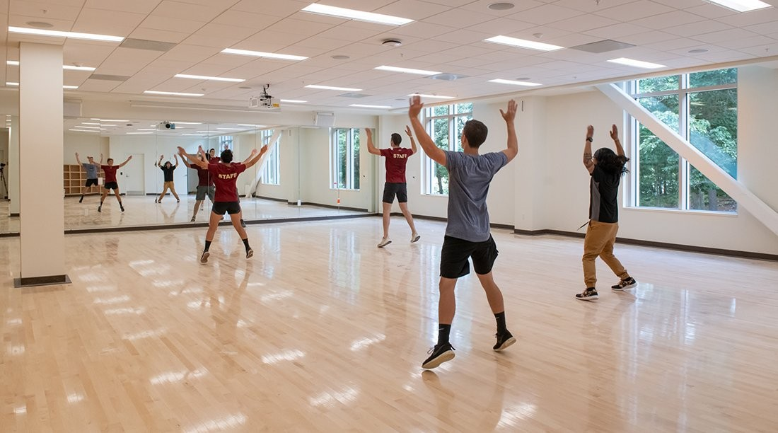 Students doing jumping jacks in a brightly lit room