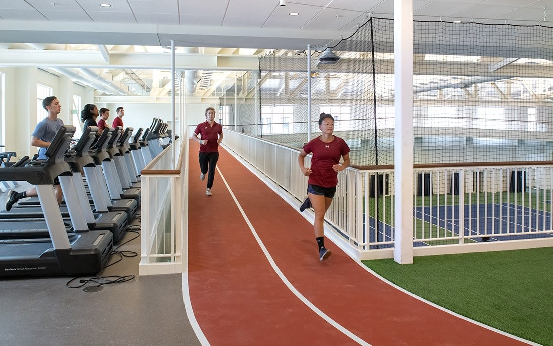 Two students running on an elevated indoor track