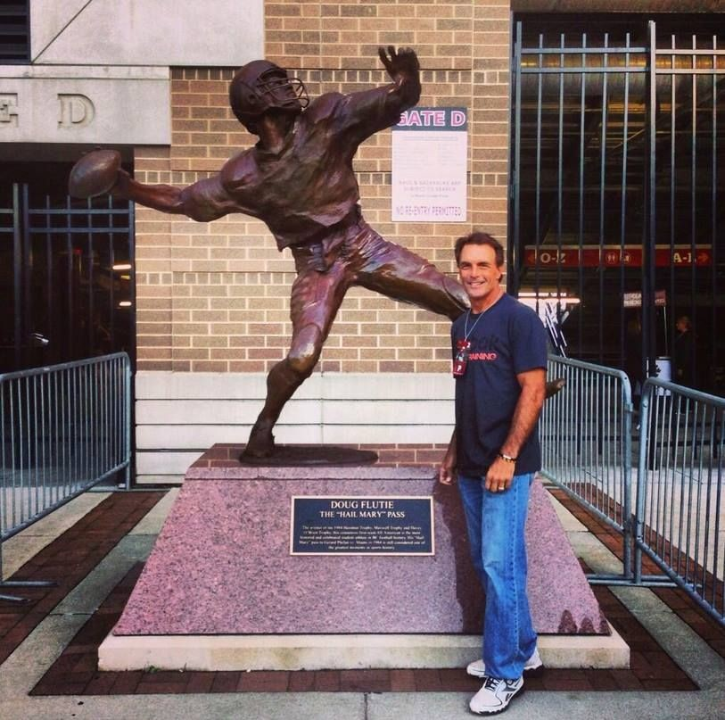 Doug Flutie in front of the campus statue in his honor.
