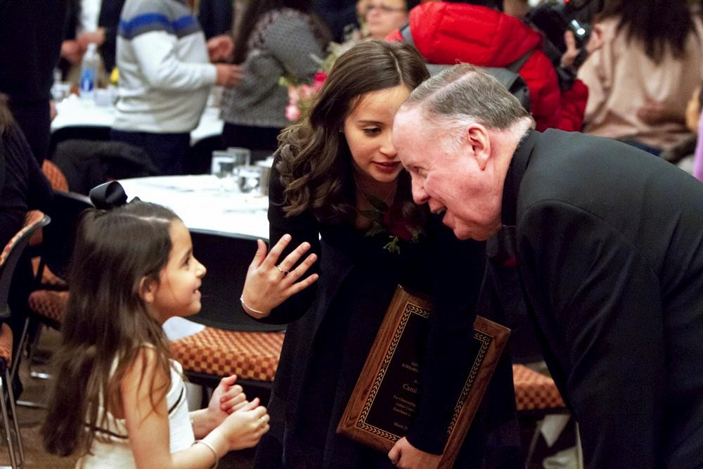 University President William P. Leahy, S.J., chats with Tiru with her little cousin Isabela Sofia Isidro at the awards banquet.