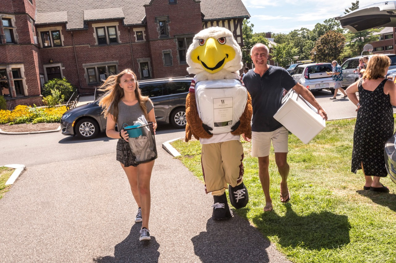 Baldwin, here with Elyse Messick '21 and her dad, Chip, pitches in on Upper Campus.