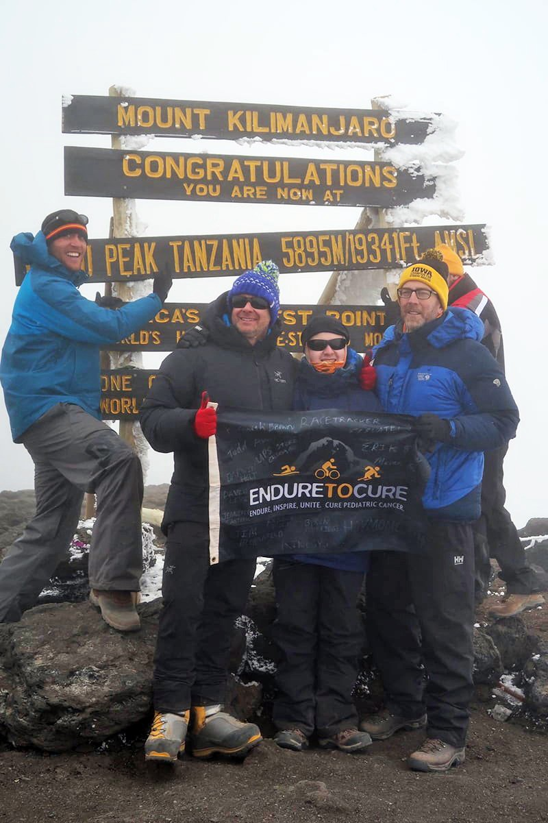 "Nick Claudio and Jason Sissel holding an ""Endure to Cure"" Banner with other hikers at the summit."