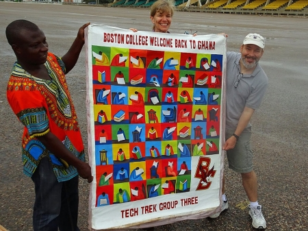 BC TechTrek Ghana leaders John Gallaugher and Elizabeth Bagnini with a welcome banner presented as a gift from bus driver Alex Asare, who has been with the program for three years.