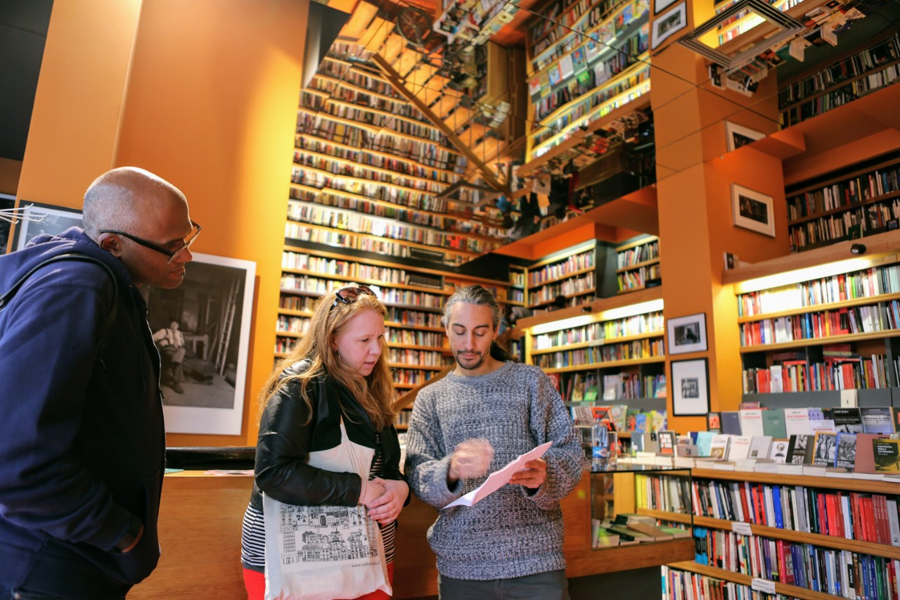 Associate Professor of the Practice of English and poet Alison Adair talks with Chilean poet Jorge Rosemary at the Ulises bookstore in Santiago. Looking on is Associate Professor of History Martin Summers.