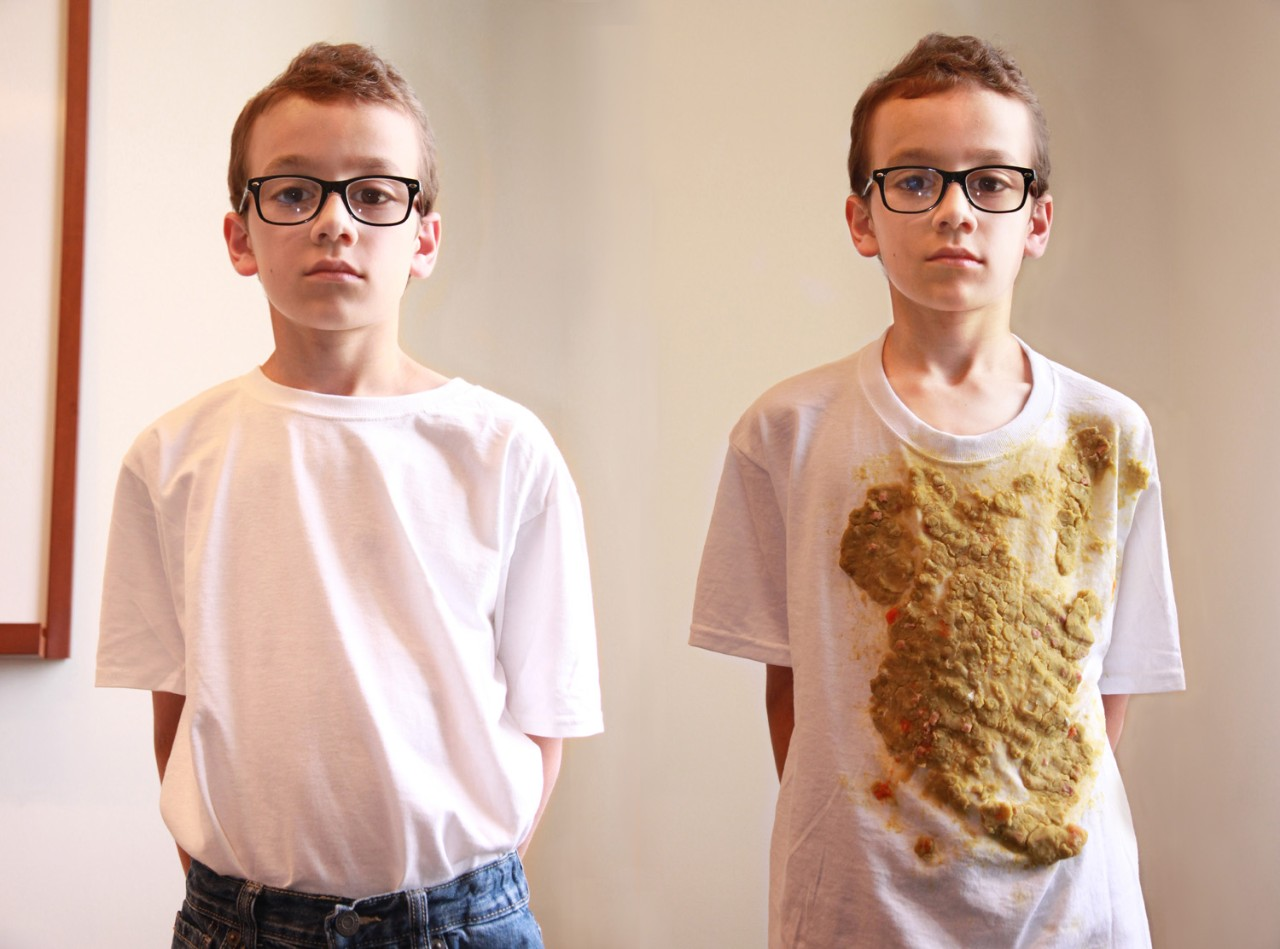 Two identical young boys, one wearing a clean t-shirt, the other wearing a dirty t-shirt