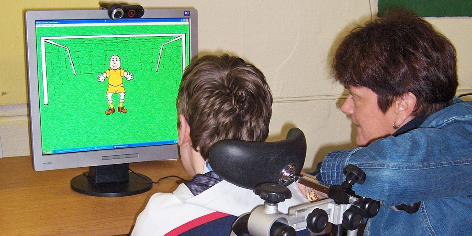 Patrick, a student at the School of the Divine Child in Cork, Ireland learns to use Camera Mouse with teacher Maureen Gates