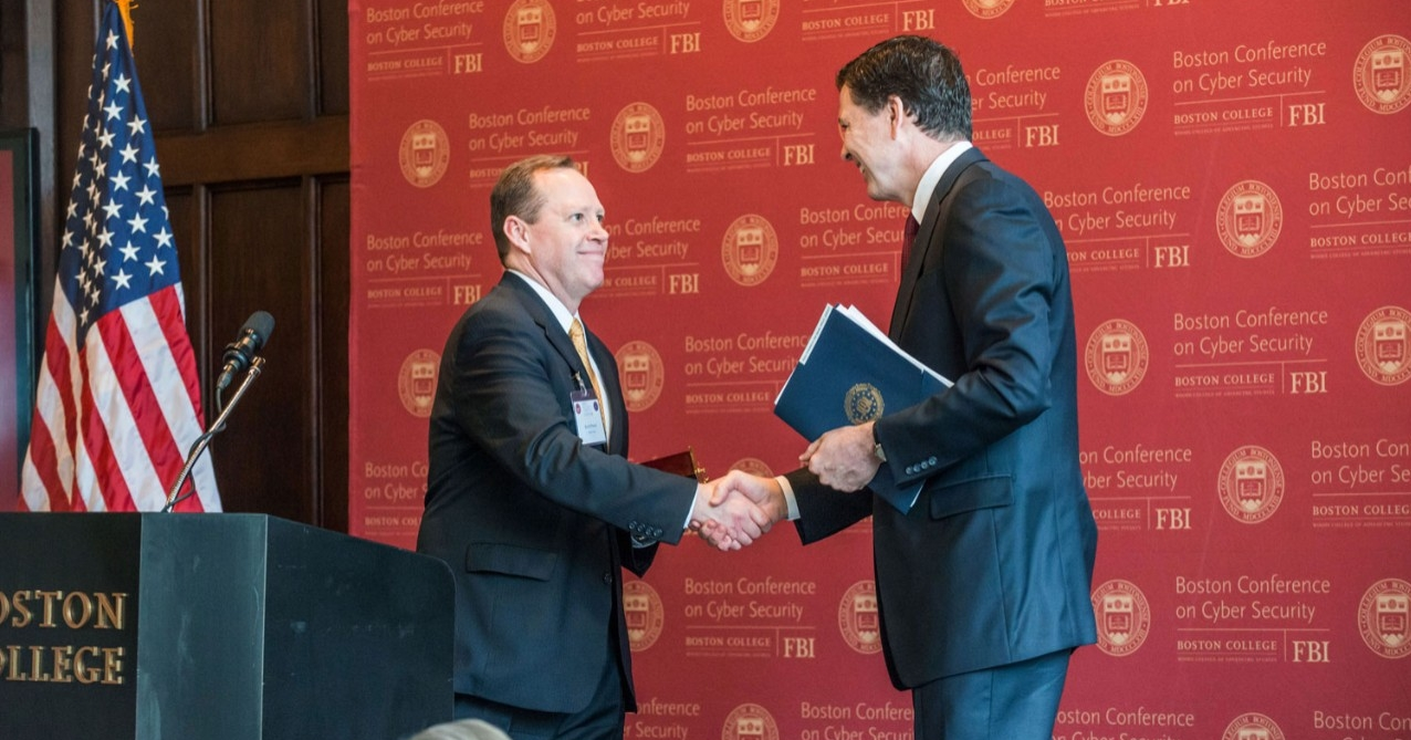 Conference organizer Kevin Powers, founding director of the Woods College Cybersecurity Policy & Governance program, with FBI Director Comey.