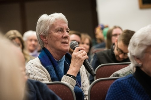 A member of the audience poses a question to the panelists.