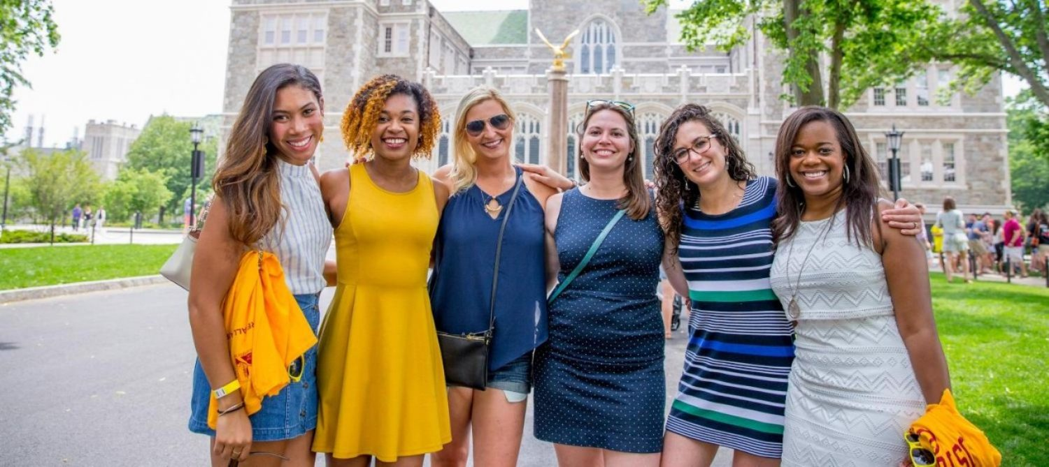 six people standing arm in arm in front of gasson hall