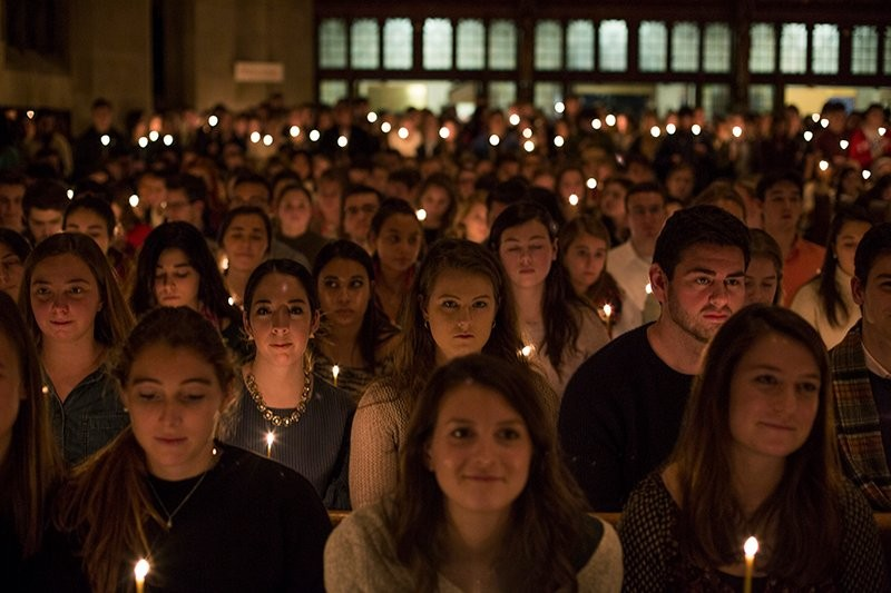 A group of students holding candles during mass