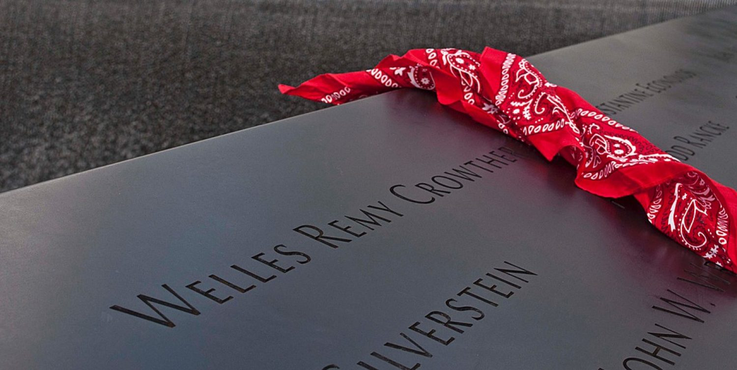 A red bandana draped over a granite marker