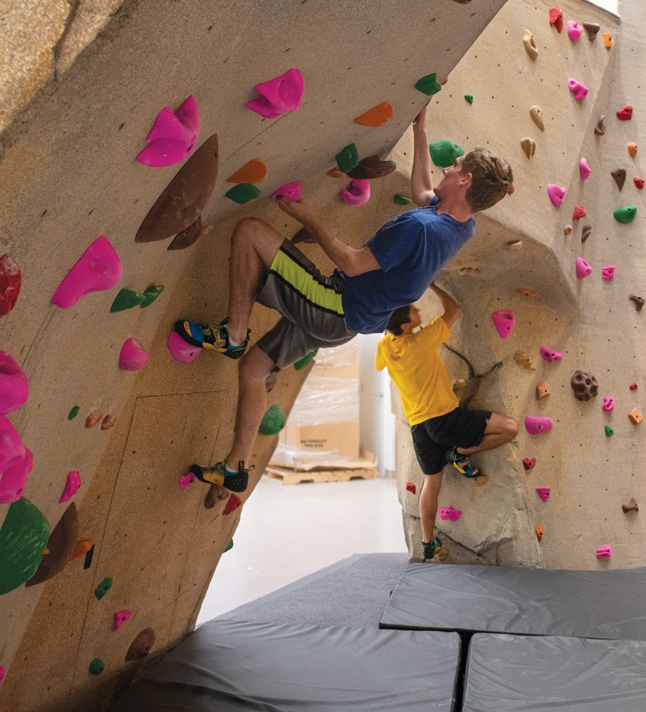 man helping woman on climbing wall