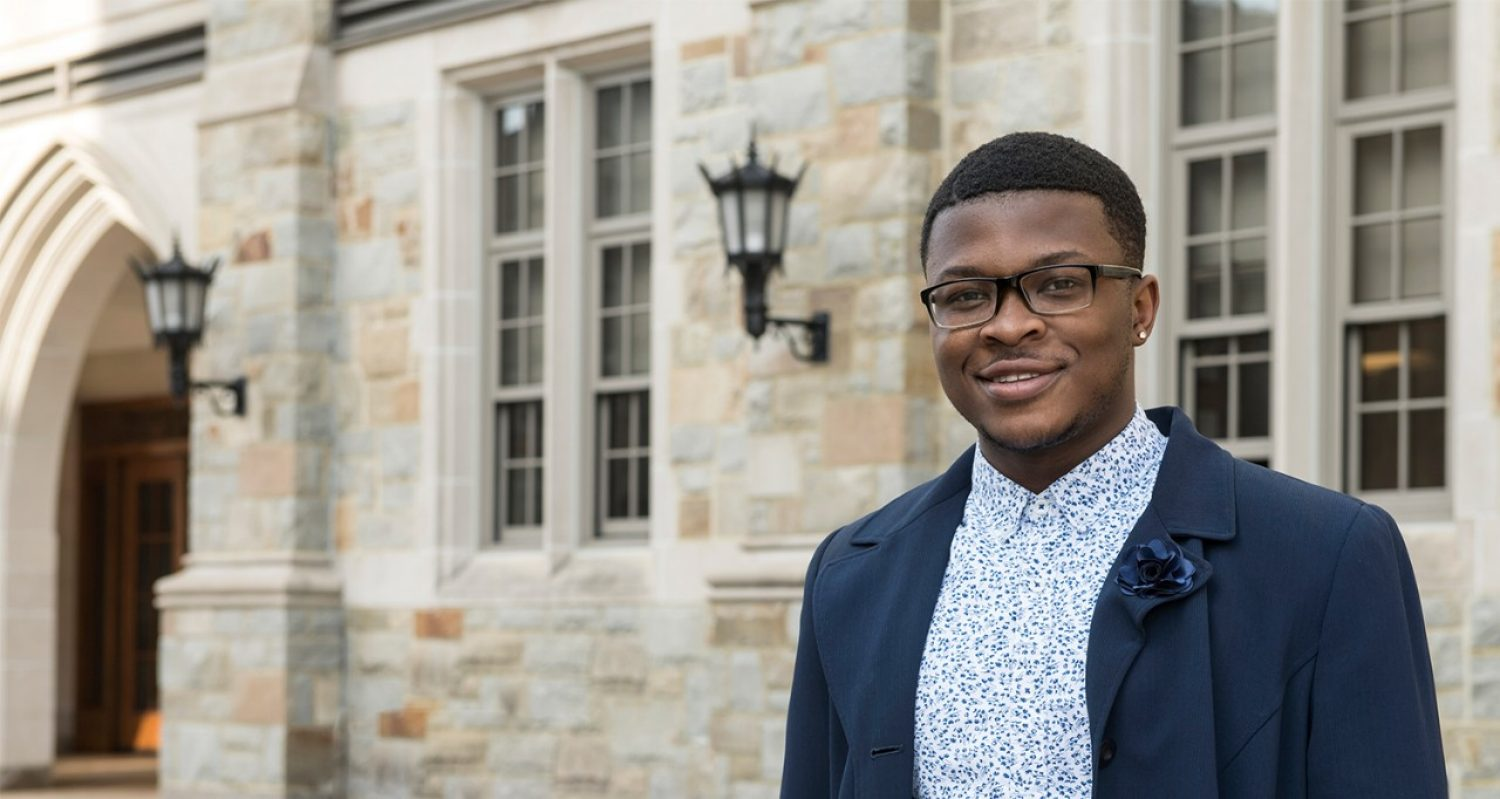 Kofi Nimo, a young black man in glasses and a button down with a jacket, stands in front of Fulton Hall