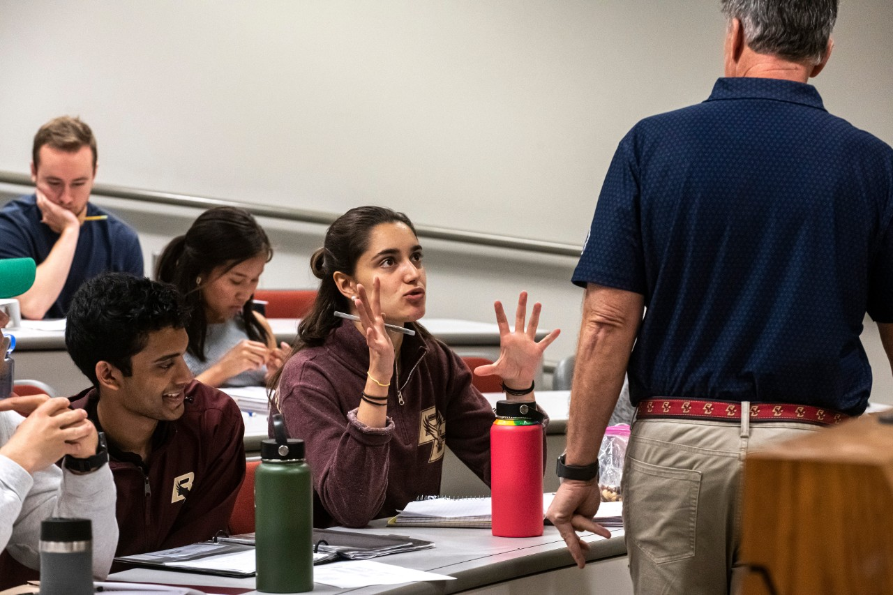 Students sit in a classroom. At the center of the image a student in a BC sweatshirt is talking with her hands gesturing in front of her face. The professor from the previous photo is standing facing her with his back to the camera