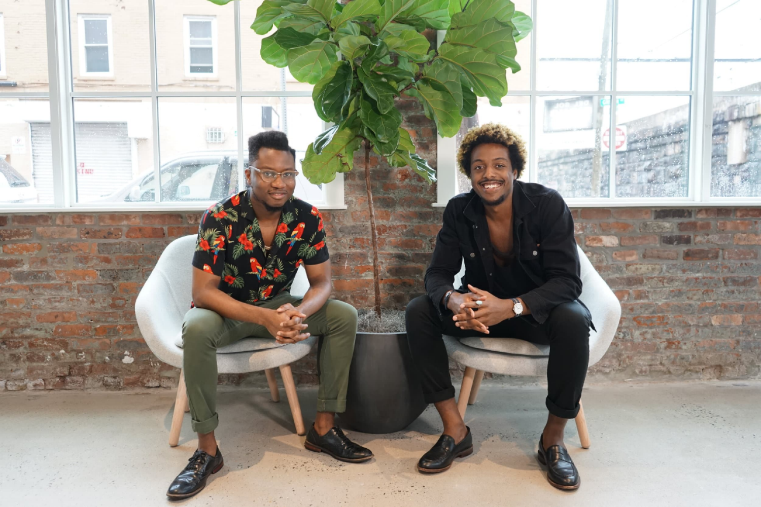 Ivan Alo and LaDante McMillon sitting in their office in front of a large plant