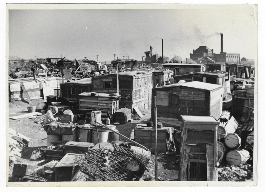 Black and white photo of a dump, which includes a number of dilapidated shacks and barrels.