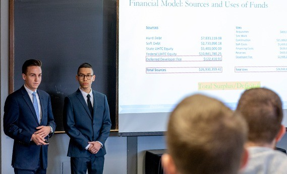 Two college students at the front of a classroom present in the 2019 Corcoran Case Competition