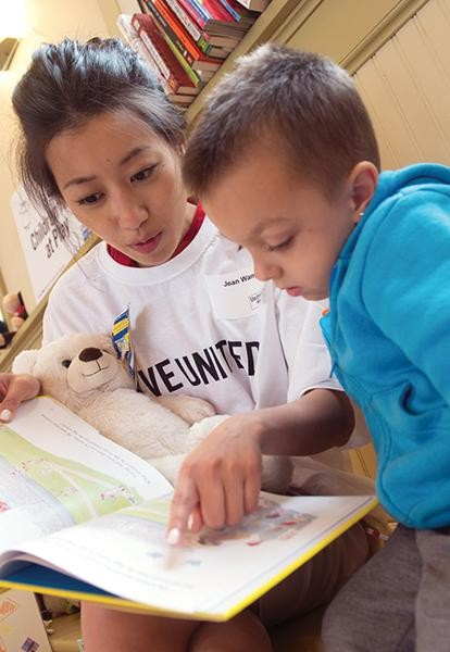 an asian woman in a United Way tshirt reads to a child
