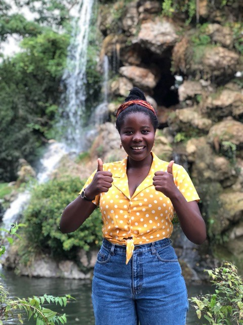 Liliane standing in front of a waterfall giving two thumbs up