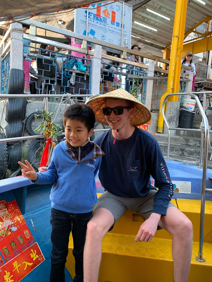 Austin and a young boy in a crowded market. Austin is wearing a traditional Asian rice hat