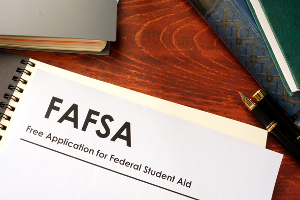 Photograph of a FAFSA booklet on desk next to a pen