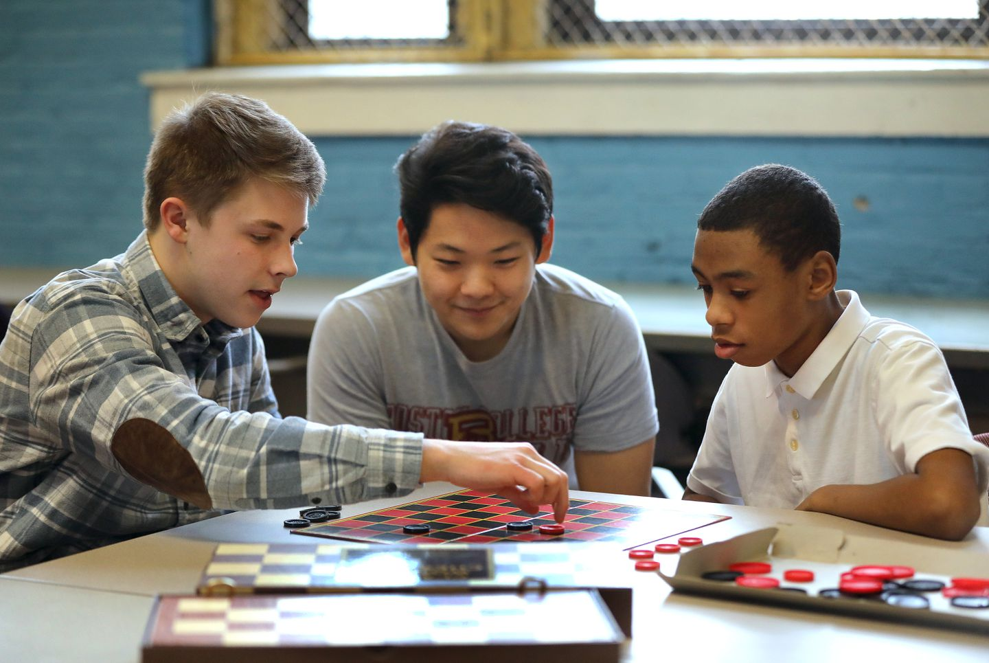 Photo of student volunteering and playing checkers