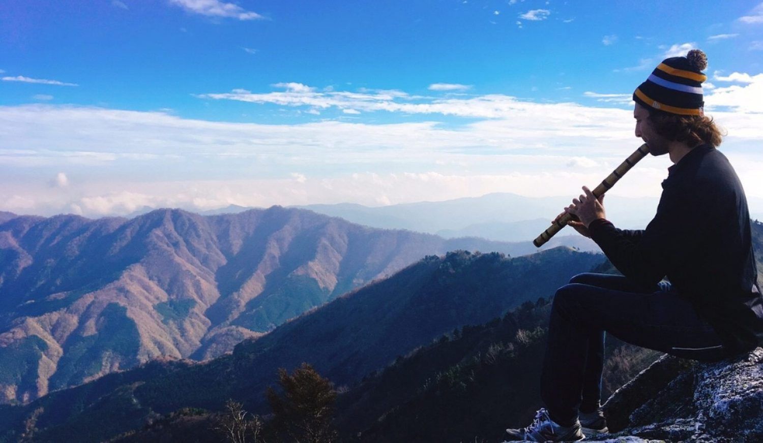 Student playing an instrument on a mountain top