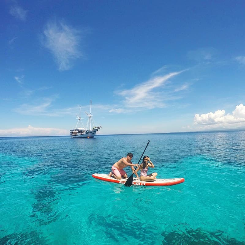Liana Lopez '20 paddleboards over clear waters in Apo Island, Dumaguete, one of seven thousand islands in the Philippines