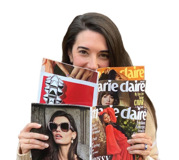 Sally Holmes holding three Marie Claire magazines.