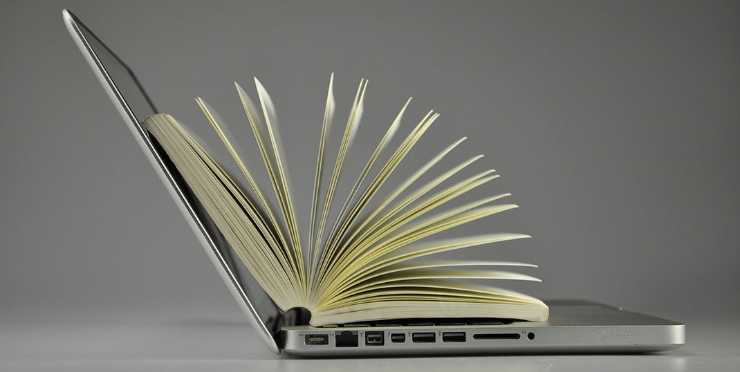 An image of a laptop with paper pages coming out of it
