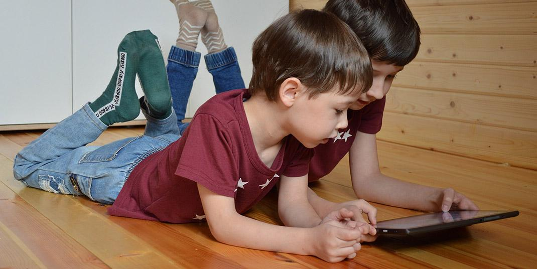 Two young kids looking at a tablet