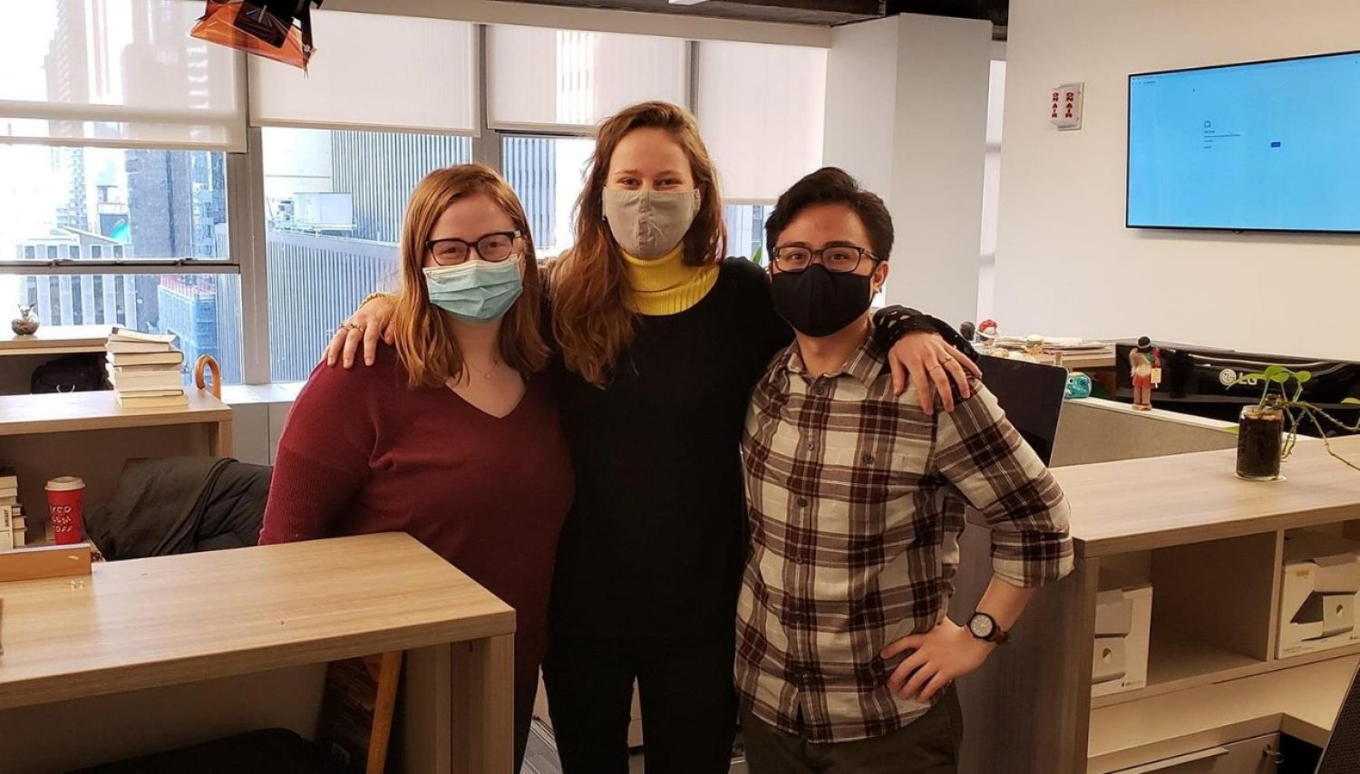 Three people wearing masks standing in an office
