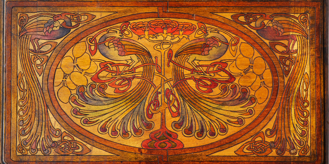 Eva McKee (b. 1890), Panel (box lid) with peacocks, flowers, and Celtic interlace, c. 1900–25 Wood decorated with pokerwork and stained&#x3b; 19.7 x 35.2 cm Private collection