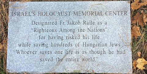 Plaque outside Sacred Heart Catholic Church commemorating Jesuit Fr. Jakob Raile's heroism during the Holocaust.
