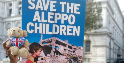 A sign reads 'Save the Aleppo Children'
