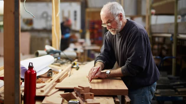 elderly retiree doing woodworking