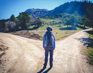 Hiker standing at a fork in a dirt road