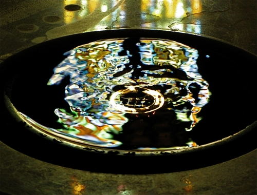 A dimly lit baptismal font with stained glass reflected on the rippled water