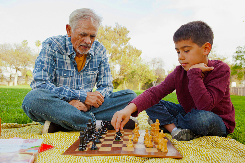 Gray-haired man playing chess with a boy