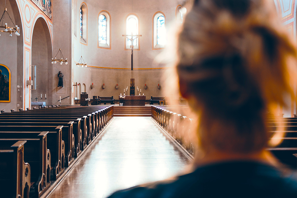 A woman looking towards the altar of an empty church