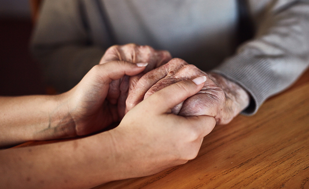 A friend holds the hand of an older adult to offer support