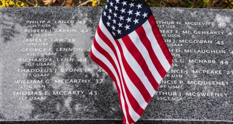 American flag draped over granite memorial