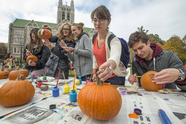 Students painting pumpkins during the fall