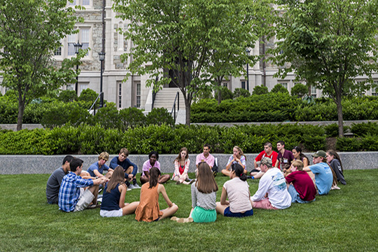 circle of students on grass in front of Gasson Hall