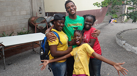 Boston College student with three Jamaican students